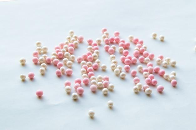 Contas de rosa e brancas bonitos estão espalhadas em branco