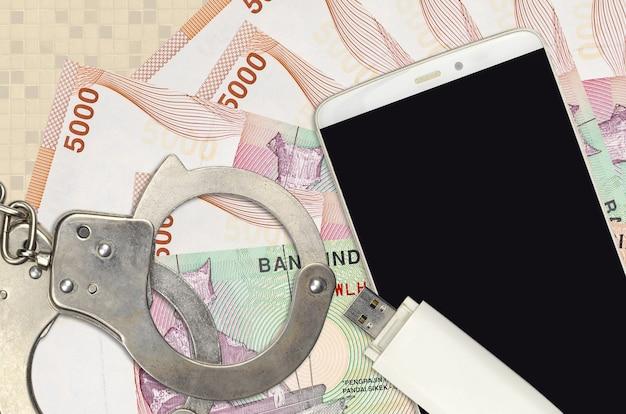 Contas de rupia indonésia e smartphone com algemas policiais