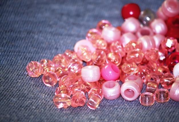 Contas de vidro e plástico rosa e vermelhas para decoração.