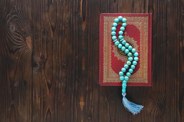 Contas do alcorão e rosário na mesa de madeira