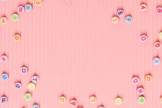 Contas do alfabeto contornam papel de parede rosa espaço de texto