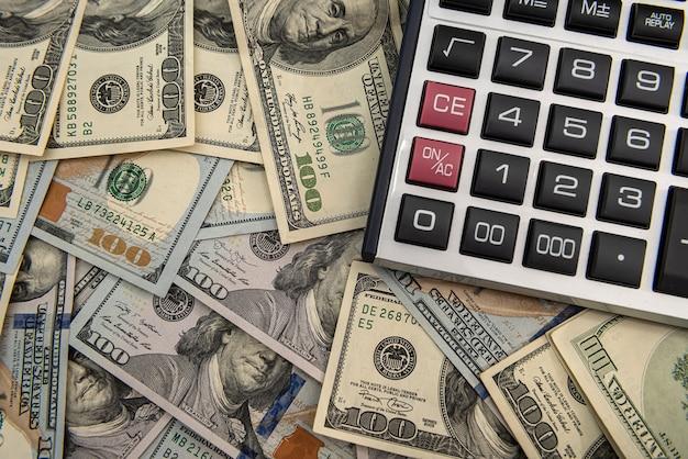Contas e calculadora em dólares americanos, conceito de investimento ou poupança