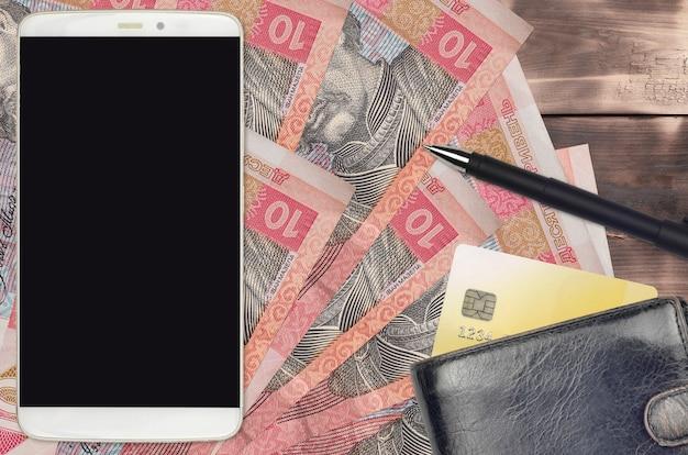 Contas hryvnias ucranianas e smartphone com bolsa e cartão de crédito