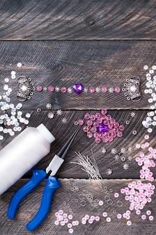 Contas, pingentes, alicate, corações de vidro e acessórios para criar joias feitas à mão em mesa de madeira, fazendo pulseira