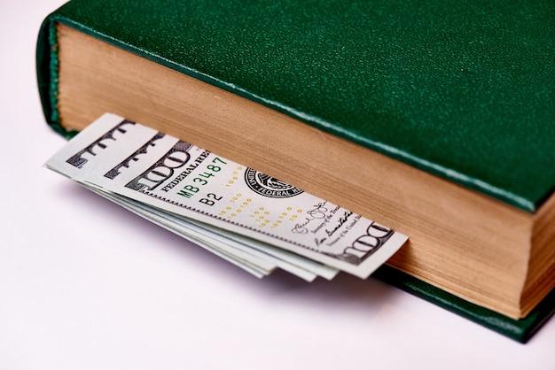 Contas que valem cem dólares americanos no livro em uma macro branca do fundo.