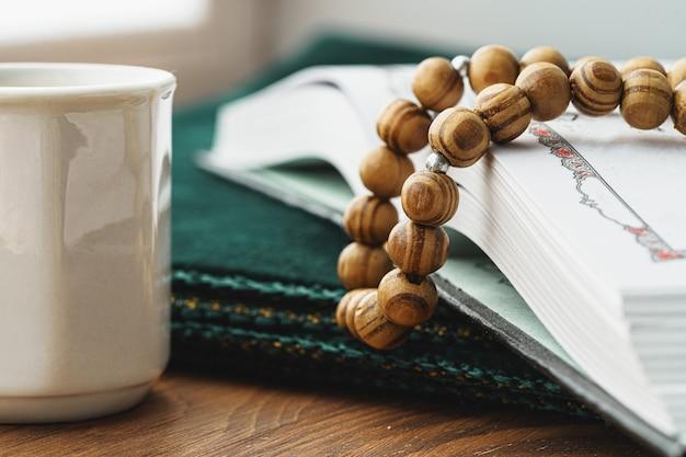 Contas religiosas orientais fecham-se sobre uma mesa de madeira com café