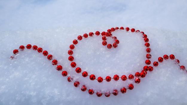 Contas vermelhas brilhantes em forma de coração na neve branca perfeita dia dos namorados natal ano novo