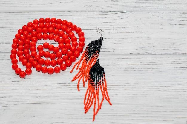 Contas vermelhas grandes em um colar com brincos artesanais em um fundo de madeira.