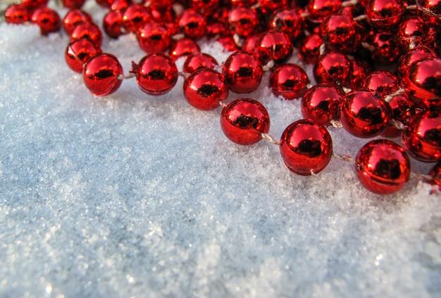 Contas vermelhas no canto de um fundo de neve fresca em um dia ensolarado para copiar o texto de suas palavras