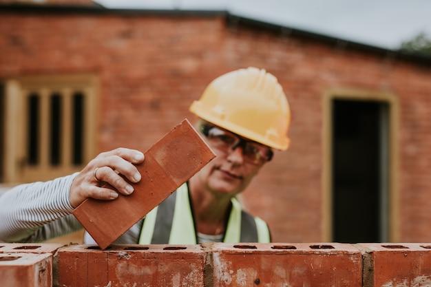 Contator mulher colocando tijolos fora de casa