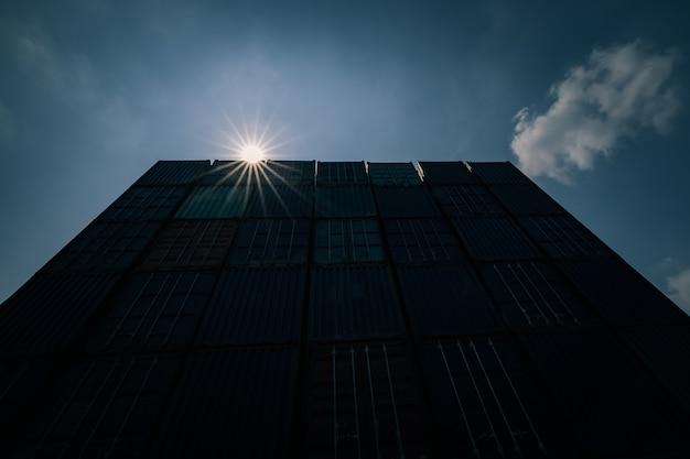 Contêiner de transporte de silhueta com dom de sol claro céu azul plano de fundo grande angular foto tom de sombra escura