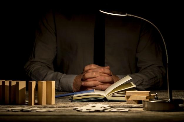 Contemplação ou resolução de problemas com as mãos postas perto de um livro e peças do quebra-cabeça sob a luminária de mesa.