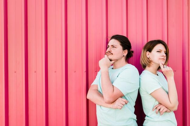 Contemplado jovem casal em pé contra a parede de ferro vermelho