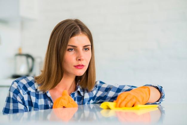 Contemplado jovem mulher usando luvas segurando o guardanapo sobre a mesa branca