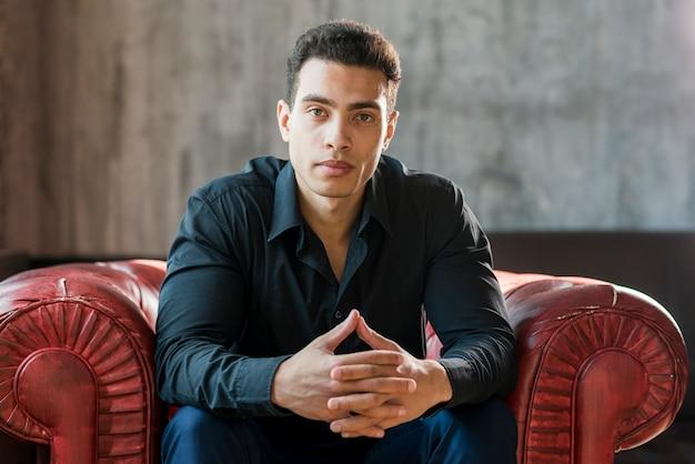 Contemplado jovem sentado na poltrona vermelha com a mão contra a parede