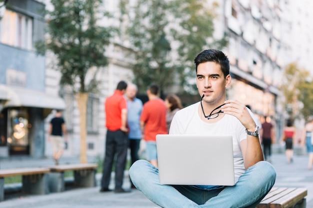 Contemplado jovem sentado no banco com laptop