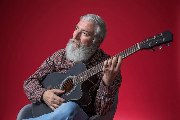 Contemplado sênior homem tocando violão contra o fundo vermelho