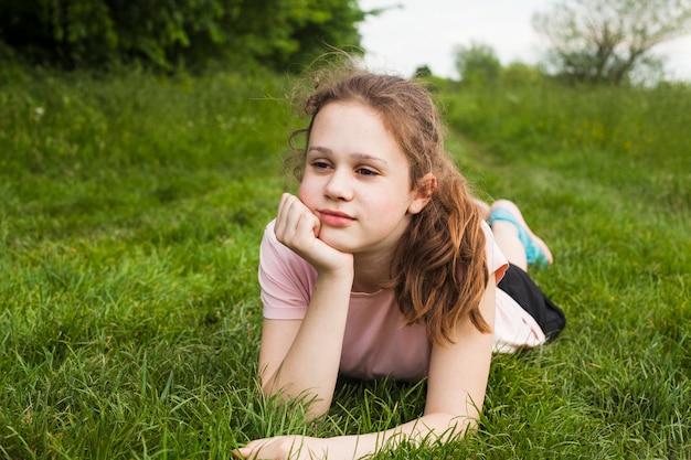 Contemplando a menina bonita deitada na grama verde no parque