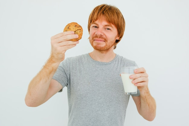 Content red-haired man eating cookie com leite