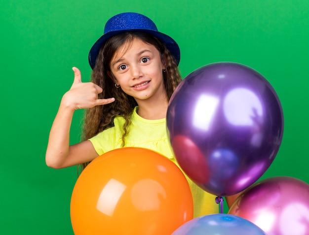 Contente garotinha caucasiana com chapéu de festa azul segurando balões de hélio e fazendo gestos de soltar isolados na parede verde com espaço de cópia
