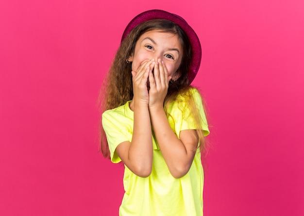 Contente garotinha caucasiana com chapéu de festa roxo cobrindo a boca com as mãos isoladas na parede rosa com espaço de cópia
