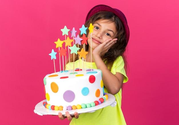 Contente garotinha caucasiana com chapéu de festa roxo segurando bolo de aniversário e colocando a mão no rosto isolado na parede rosa com espaço de cópia