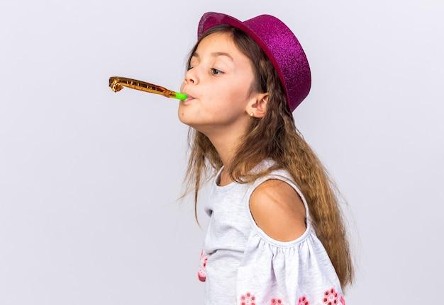 Contente garotinha caucasiana com chapéu de festa roxo soprando apito de festa olhando para o lado isolado na parede branca com espaço de cópia