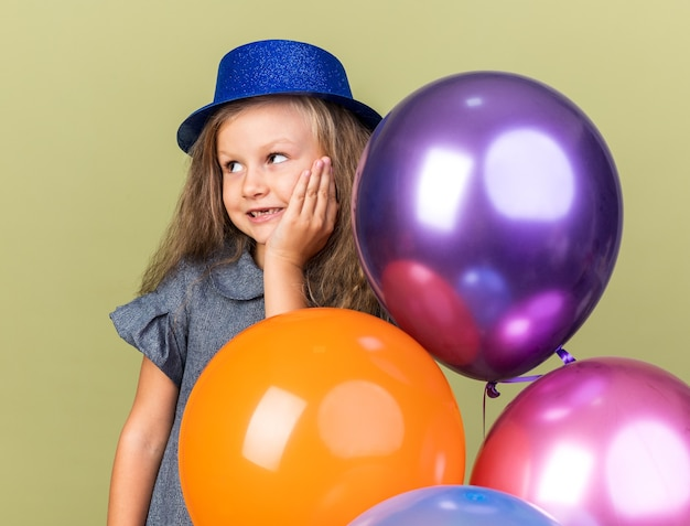 Contente garotinha loira com chapéu de festa azul em pé com balões de hélio colocando a mão no rosto e olhando para o lado isolado na parede verde oliva com espaço de cópia