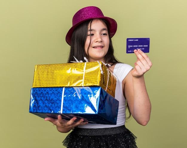 Contente jovem caucasiana com chapéu de festa roxo segurando caixas de presente e olhando para o cartão de crédito isolado na parede verde oliva com espaço de cópia