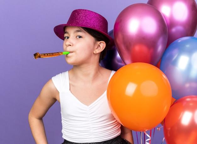 Contente jovem caucasiana com chapéu de festa violeta segurando balões de hélio e soprando apito de festa isolado na parede roxa com espaço de cópia