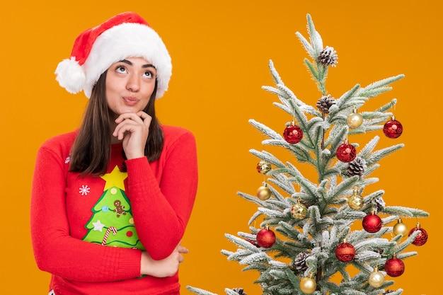 Contente jovem caucasiana com chapéu de papai noel coloca a mão no queixo, olhando para cima em pé ao lado da árvore de natal isolada em um fundo laranja com espaço de cópia
