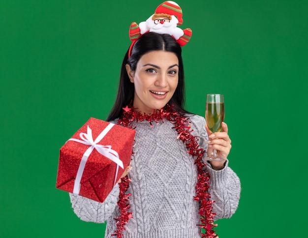Contente, jovem, caucasiana, vestindo uma bandana de papai noel e guirlanda de ouropel no pescoço, estendendo o pacote de presente e segurando uma taça de champanhe isolada na parede verde