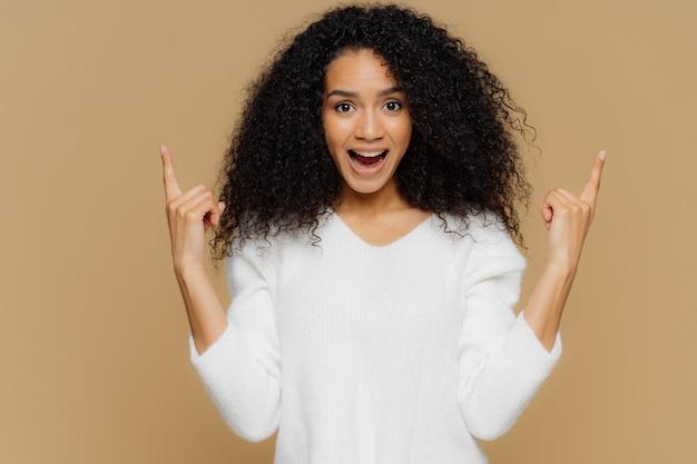 Contente jovem fêmea aponta para cima com os dedos indicadores, mostra item impressionante à venda