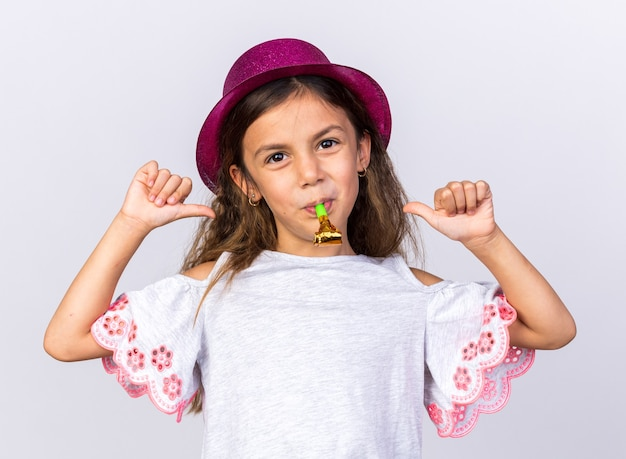 Contente menina caucasiana com chapéu de festa roxo soprando apito de festa e apontando para si mesma, isolada na parede branca com espaço de cópia