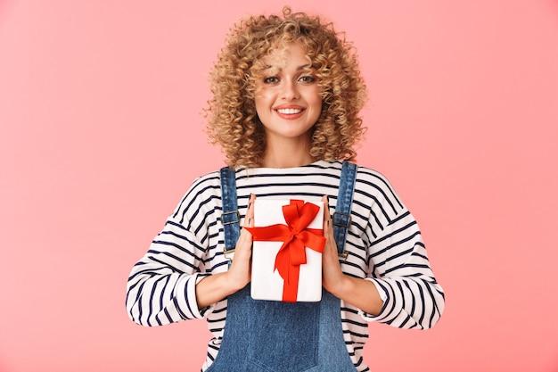 Contente mulher cacheada de 20 anos segurando uma caixa de presente em pé