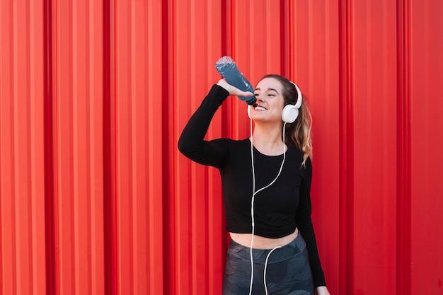 Contente mulher esportiva em fones de ouvido bebendo água