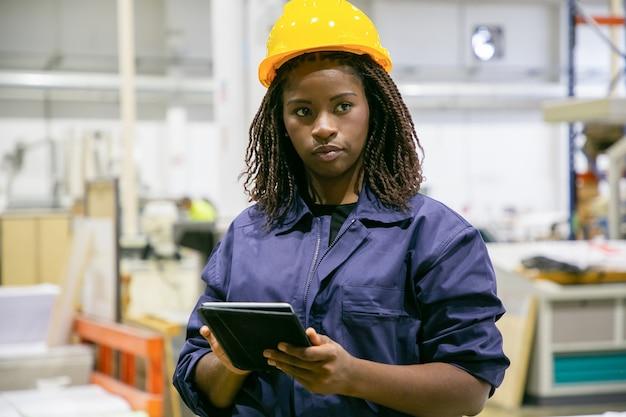 Contente, trabalhadora de fábrica em pé com um tablet e olhando para longe
