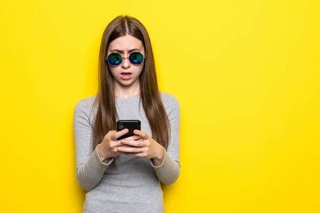 Conteúdo adolescente com cabelos longos, segura telefone celular moderno, percorre as redes sociais