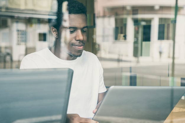 Conteúdo afro-americano sentado à mesa e usando um laptop