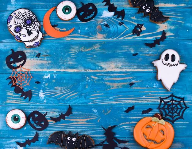 Conteúdo da festa de halloween. biscoitos de gengibre de halloween sobre o fundo azul de madeira.