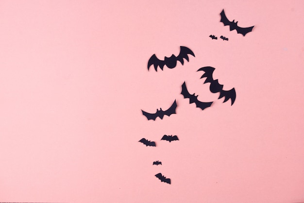 Conteúdo da festa de halloween. morcegos pretos de tamanhos diferentes em um fundo rosa.