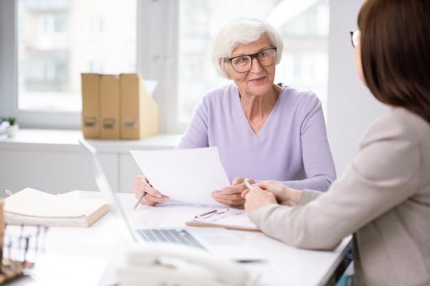 Conteúdo dama de cabelos brancos de óculos, sentada à mesa e aconselhando sobre problemas documentais com a assistente social
