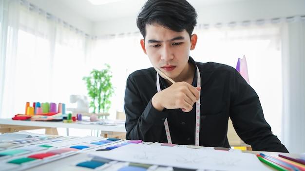 Conteúdo de designer de roupas masculinas étnicas sentado a uma mesa com amostras de tecido e esboços