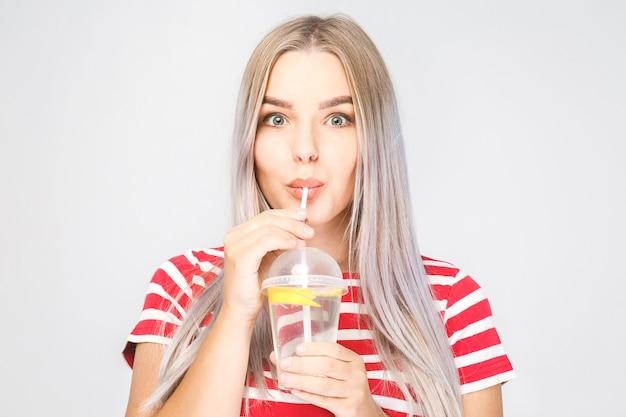 Conteúdo de saúde, pessoas, comida, esportes, estilo de vida e beleza - mulher jovem sorridente com um copo de água com limão