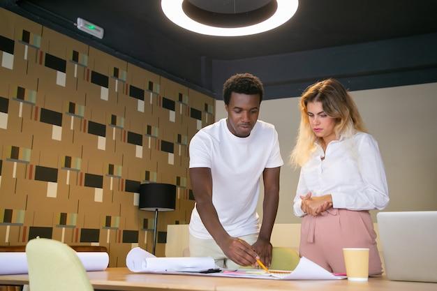 Conteúdo designer afro-americano, escrevendo a lápis no rascunho e explicando detalhes ao cliente