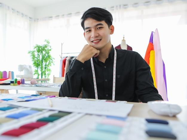 Conteúdo designer de roupas masculinas étnicas sentado à mesa com amostras de tecido e esboços enquanto.