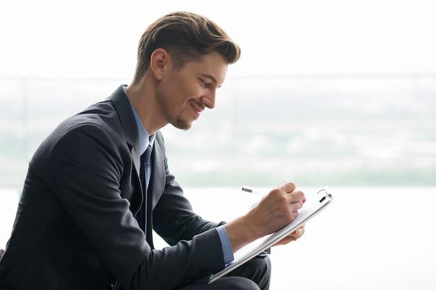 Conteúdo do homem de negócios que faz anotações meia-idade