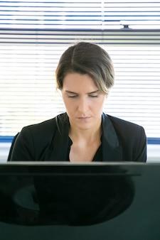 Conteúdo feminino ceo sentado e trabalhando no computador. bem sucedida pensativa linda empresária fazendo seu trabalho, pensando e olhando para baixo no monitor. conceito de negócio, expressão e fluxo de trabalho