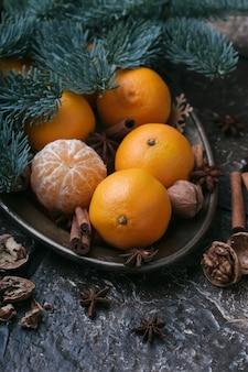 Conteúdo festivo, tangerinas, nozes, canela, cardamomo, prato de metal, galho de abeto, fundo marrom escuro, vertical