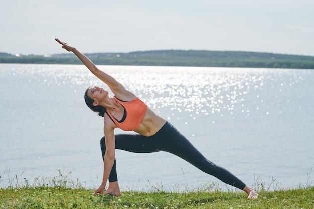 Conteúdo jovem ativa em roupas esportivas em pé na grama contra a água e levantando o braço enquanto fortalece o corpo com ioga